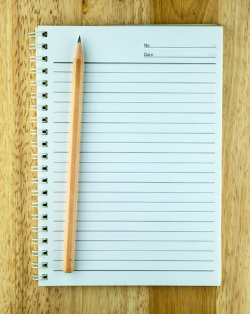 note pad with pencil on wooden background photo