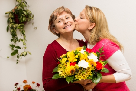 Daughter kissing her mother photo