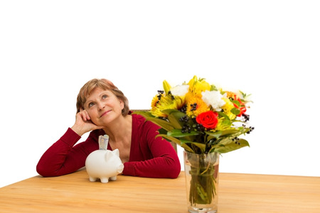 financially: Pensioner sitting with a piggy bank on a table Stock Photo