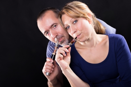 A man and a woman with e-cigarettes