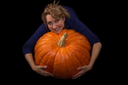 Female hugging a huge pumpkin photo