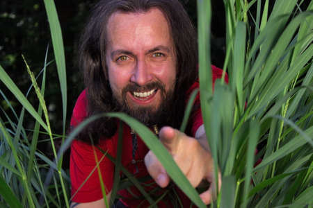long haired: Long-haired man pointing out of high gras Stock Photo