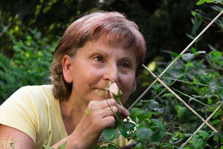 Retiree smmelling on a rose in her garden