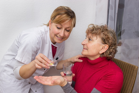 doses: Doctor giving pills to a pensioner Stock Photo