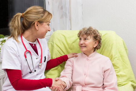 outpatient: Nurse holding the hand of an old woman
