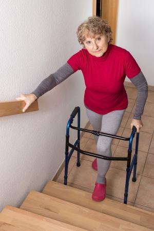 Důchodce stojící s Walkerem před schodiště Reklamní fotografie