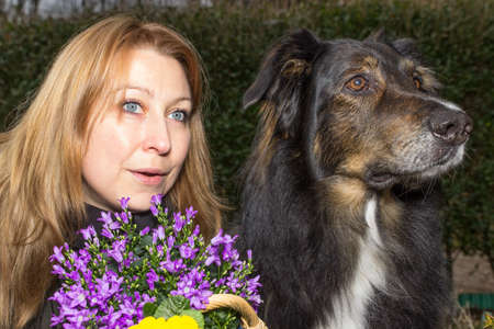 heralds: Female holding a flower basket looking curious with her dog