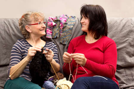 crochet: Two girlfriends knitting together on a couch Stock Photo