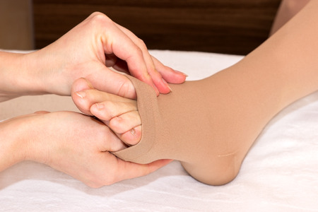 Assistance by putting on DVT stockings photo