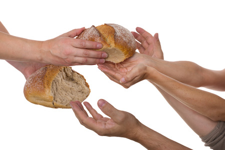 Many hands grabbing for bread
