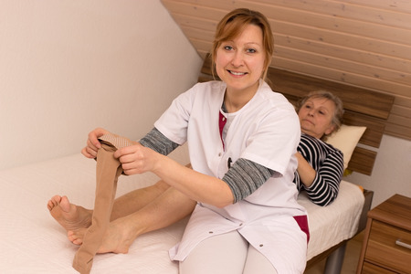 Geriatric nurse helps pensioner during tightening anti-thrombosis stockings photo