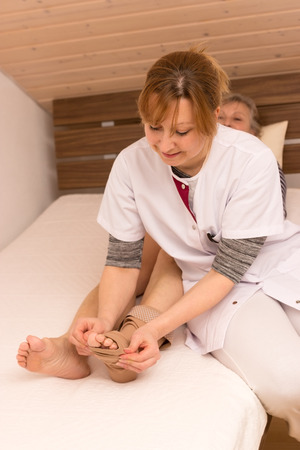 Nurse helps older woman in the bed photo