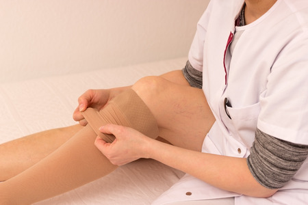 tedious: Caregiver helps somebody putting antithrombotic stockings on Stock Photo