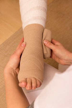 A pressure bandage is beeing applyed by a nurse photo