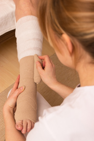 A nurse is applying a pressure bandage on a leg Stock Photo