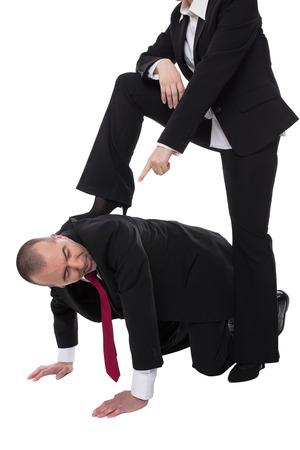 arrodillarse: El hombre de rodillas en el suelo, la mujer se encuentra con un pie en la espalda Foto de archivo