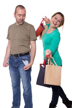 bolsillos vacios: El hombre est� de pie con los bolsillos vac�os al lado de una mujer con bolsas de la compra con relleno