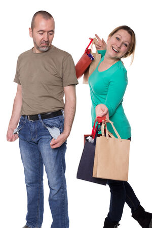 empty pockets: Man stands with empty pockets next to a woman with filled shopping bags