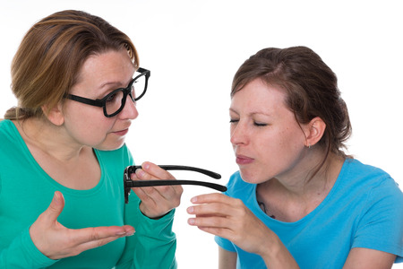 Woman hands over another woman a glasses