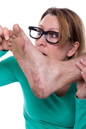 Woman looks at the dirty foot of a man photo