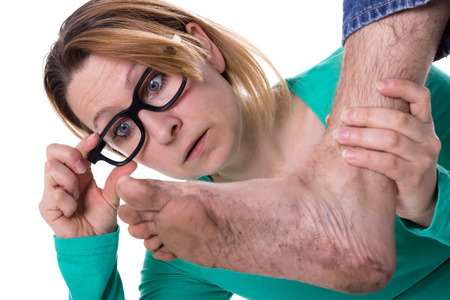 stench: Woman with glasses is astonished about a dirty foot