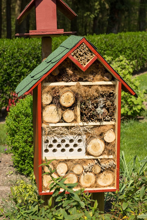 wintering: An insect hotel in a green landscaped garden Stock Photo