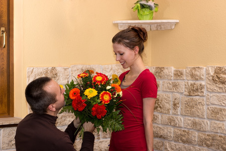 gives: Kneeling man gives a young woman a bouquet of flowers Stock Photo
