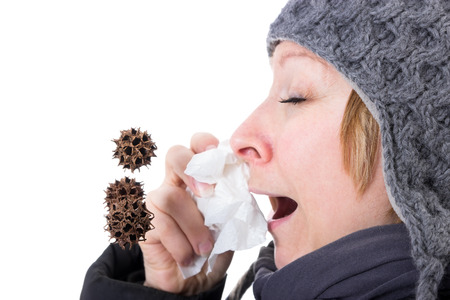 By a woman sneezing viruses and bacteria flying through the air