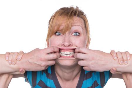 femme bouche ouverte: Femme se défend contre deux mains ouvrant sa bouche Banque d'images
