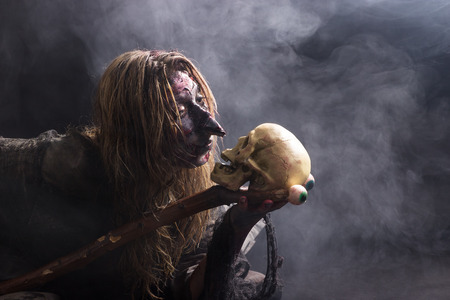 summoning: A witch conjures up a skull in the fog