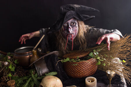 bewitch: Witches bends over a table with witches ingredients Stock Photo