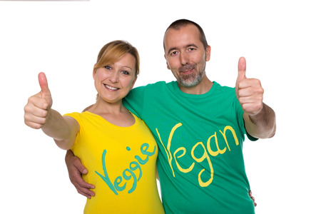A couple with the inscription vegan and veggie on the t-shirts, stretch thumbs up Imagens