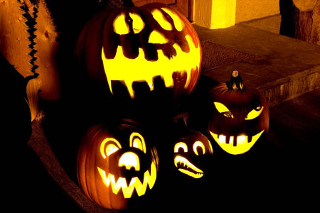 mummery: Several illuminated Halloween pumpkins at the entrance of a house Stock Photo