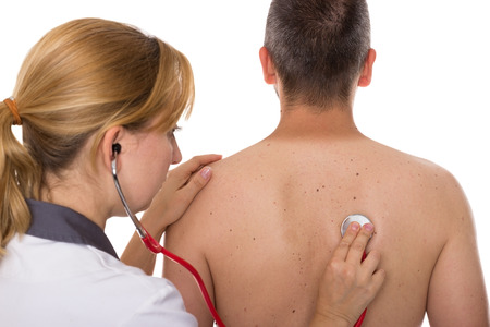 respiratory tract: A doctor auscultates a male patient from behind Stock Photo