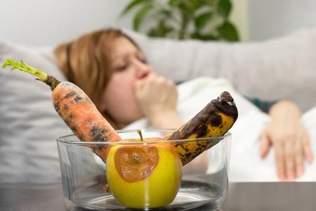 Žena má bolesti žaludku kvůli shnilé ovoce a zeleniny