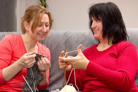 jointly: Two female knitting together on a couch at home