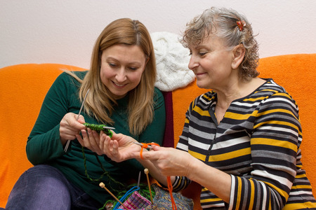 family sofa: Young and old knitting and crocheting together