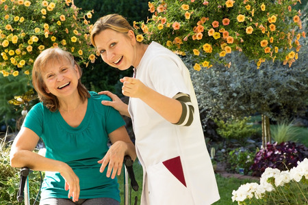 Senior and their nurse standing in the garden and pointing at camera