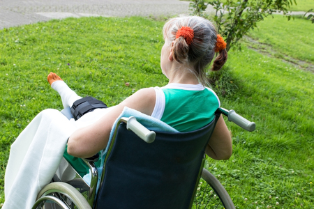 mobility nursing: A woman in a wheelchair alone in a park