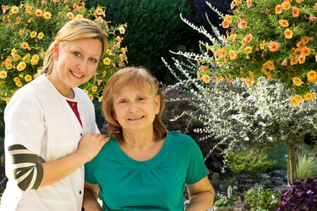 socially: One Senior is beeing supervised by a nurse in a garden Stock Photo