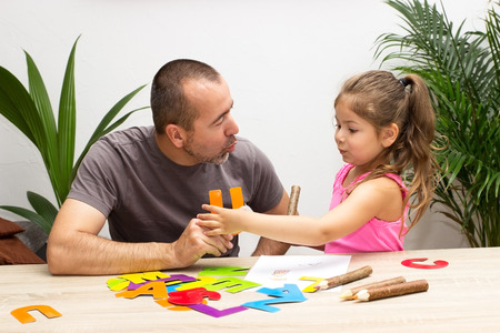to speak: A little girl is practicing the alphabet with her father Stock Photo