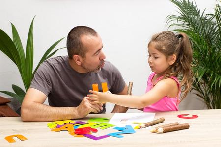 Holčička se cvičí abecedu s jejím otcem Reklamní fotografie