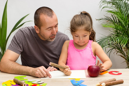 father daughter: A father is exercising the alphabet with his little daughter