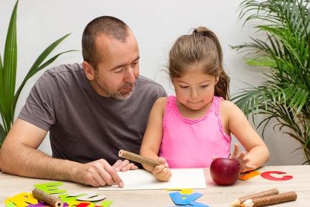 ni�os con l�pices: Un padre est� ejerciendo el alfabeto con su peque�a hija Foto de archivo