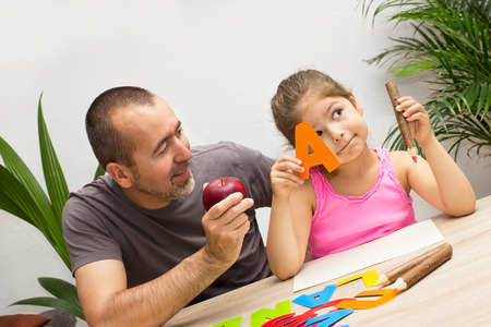 A little girl learns the alphabet playful with her dad Stockfoto