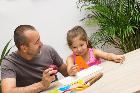 Otec a dcera cvičit abecedu s ovocem