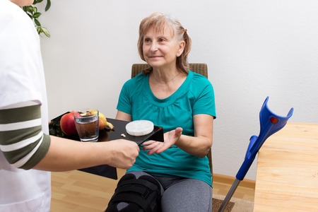 assisted living: A nurse brings a tray with fruit and medicines to a handicaped patient