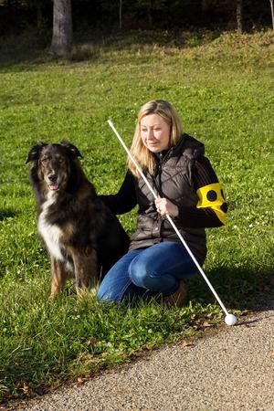 Průvodce pes sedí vedle slepé ženy, na louce