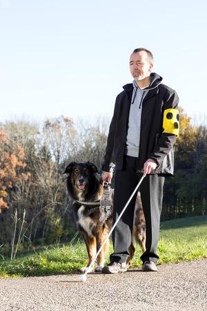 Een blinde man gaat voor een wandeling met zijn geleidehond Stockfoto