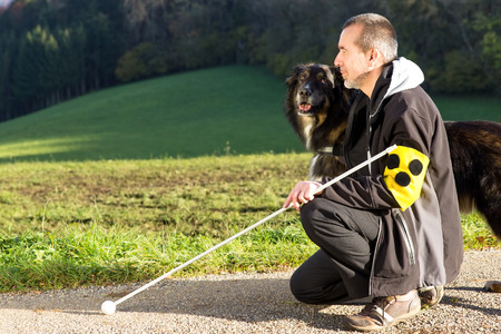 A blind man kneels next to his attentive guide dog